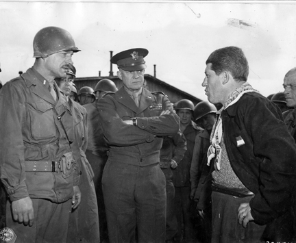 April 12, 1945 - DDE listens as 1st LT. Alois J. Liethen of Appleton, WI, who served as the interpreter for the tour of Ohrdruf, questions their guide