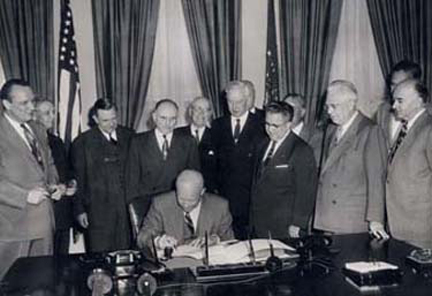 May 6, 1954 - DDE signs H.R. 8127. Standing behind DDE from left to right: Sen. Styles Bridges, Rep. George A. Dondero, Rep. Clifford Davis, Sen. Francis Case, Rep. Homer Angell, Sen. Edward Martin, Rep. J. Harry McGregor, Sen. William Knowland, Sen. Prescott Bush, and an unidentified man.