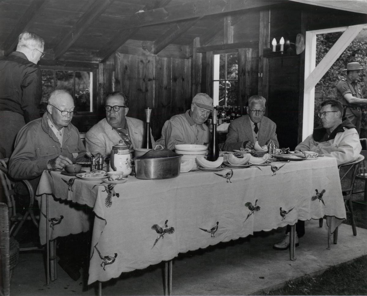 Dwight D. Eisenhower, unknown man, W. Alton Jones, Howard Snyder, and James Hagerty eat dinner. Eisenhower, George Allen, William E. Robinson, James Hagerty, and Howard Snyder were guests of W. Alton Jones at his Hianolands Farms Estate, West Greenwich, Rhode Island. September 19, 1958.