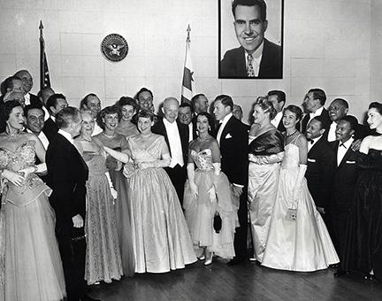 January 20, 1953 - Dwight D. Eisenhower and Mamie Eisenhower pose with guests attending the Inaugural Ball. Left to right: Guy Lombardo (standing behind an unidentified woman), Fred Waring (facing Mrs. Doud), Mrs. John S. Doud, Jeanette MacDonald, Mamie Eisenhower, Dwight D. Eisenhower, Lily Pons, and George Murphy