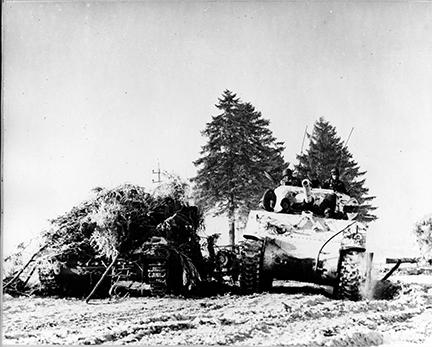 Ardennes-Battle of the Bulge. January 15, 1945 - The first tank of a tank battalion passes a knocked out German tank on the road from Bertogne to Houffalize, Belgium.