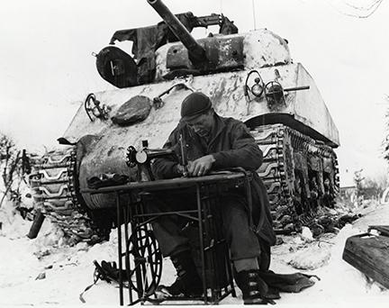 Ardennes-Battle of the Bulge. January 23, 1945 - Sgt. William Phelps of San Antonio, Texas, a tanker of the 42nd Tank Battalion, mends his combat clothes in Steinbach, Belgium. He uses a sewing machine in front of tank and snow covers the ground.