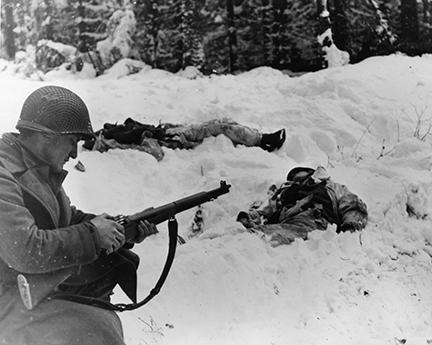 Ardennes-Battle of the Bulge. January 15, 1945 - Pfc Frank Vukasin of Great Falls, Montana, stops to load clip in rifle while advancing in snow-covered front line sector at Houffalize, Belgium. In background, two dead German soldiers are wearing camouflage snow suits.