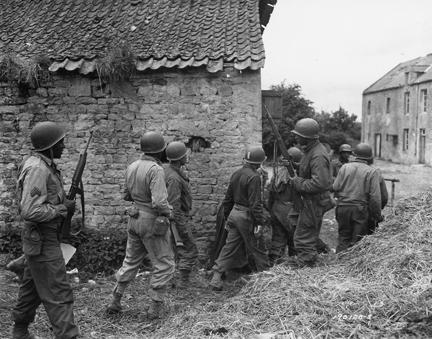 June 10, 1944 - Allied troops surround a farm house as they prepare to eliminate a German sniper holding up an advance on Omaha beachhead near Vierville-sur-Mer, France.