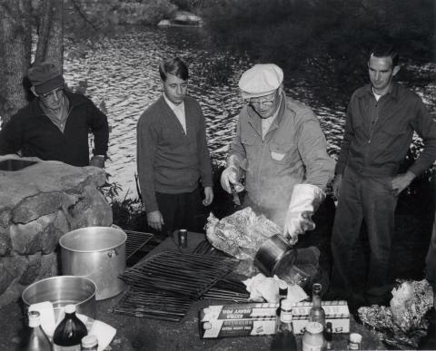 President Eisenhower cooks for friends after a fishing trip, Hianolands Farms, West Greenwich, Rhode Island, September 19, 1958.
