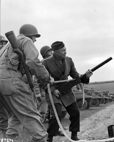 General Eisenhower fires a Browning machine gun during an inspection tour of a U.S. infantry unit at Fort Tregantle, England. February 5, 1944 [65-311]