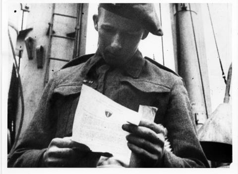 British soldier aboard ship reading Eisenhower's Order of the Day. Normandy, France, June 6, 1944. [70-233-3]