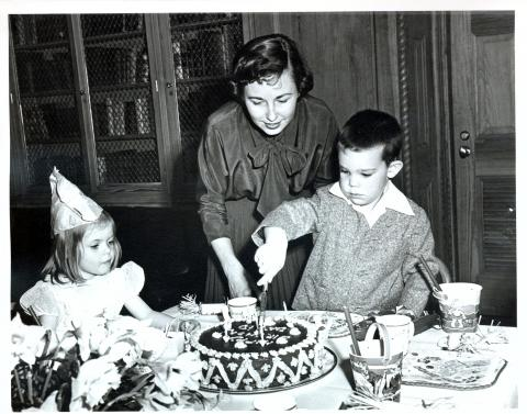 5th Birthday party for David Eisenhower held in the Library of the White House. David is cutting his cake while Mother looks on. Washington, DC, March 31, 1953 [72-172-1]