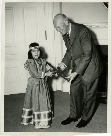 President Eisenhower received the Sword of Hope in connection with the opening of the 1957 Cancer Crusade.  Joyce Dezeller, a 6 year old Indian girl who is a cured cancer victim, presented the Cancer symbol to the President. March 29, 1957 [72-2159-1]