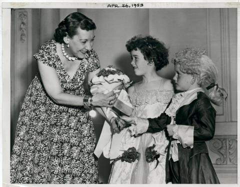 Mamie D. Eisenhower greets two children in costume representing the Children of the Revolution. April 25, 1953 [72-238-2]