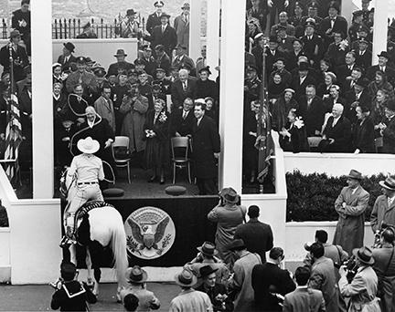 January 20, 1953 - Vice President Nixon (right) and Mamie Eisenhower (center), with big smiles, watch as Dwight D. Eisenhower is lassoed by California cowboy Montie Montana as he passed the Presidential viewing section during the Inaugural Parade