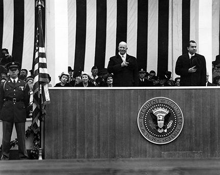 January 21, 1957 - Dwight D. Eisenhower and Richard Nixon place their hats over their hearts as the American flag passes the inaugural parade reviewing stand