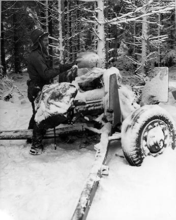 Ardennes-Battle of the Bulge. January 21, 1945 - Sgt. William Showers of Benezett, Pennsylvania, cleans the snow from the breech of his 57mm anti-tank gun in the woods near Courtil, Belgium.