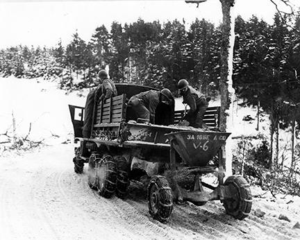 Ardennes-Battle of the Bulge. January 24, 1945 - Members of the 166th Engineers use a mechanical spreader in sanding the snow covered roads near Wiltz, Luxembourg.