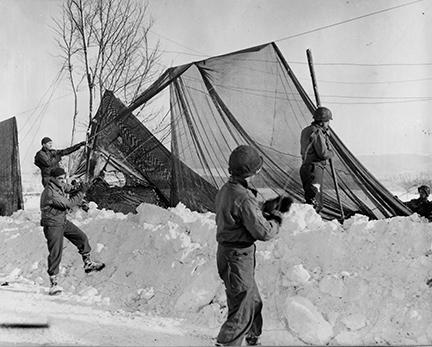 "Ardennes-Battle of the Bulge. January 23, 1945 - Restringing ""shrimp net"" road screen in the Monschau area, Germany, after a violent snow storm brought them down."