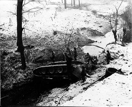 Ardennes-Battle of the Bulge. January 26, 1945 - Overturned German tank provides a bridge for 102nd Infantry Division troops crossing a small stream near Brachelen, Germany. Snow is on the ground.
