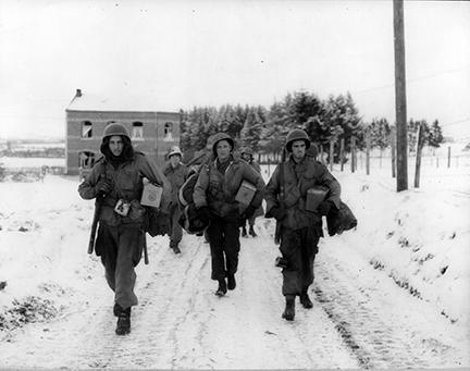 Ardennes-Battle of the Bulge. January 11, 1945 - Pfc M.L. Dickens, East Omaha, Nebraska, Pvt Sunny Sundquist, Bremerton, Washington, Sgt Francis H. McCann, Middleton, Conn., of the 101st Airborne Division near Bastogne, Belgium, set out to rejoin their unit.
