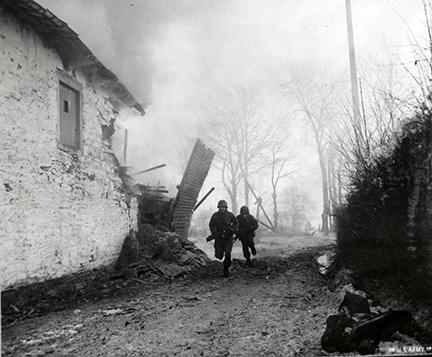 Ardennes-Battle of the Bulge. January 15, 1945 - Infantrymen of the 3rd Armored Division advance under artillery fire in Pont-Le-Ban, Belgium.