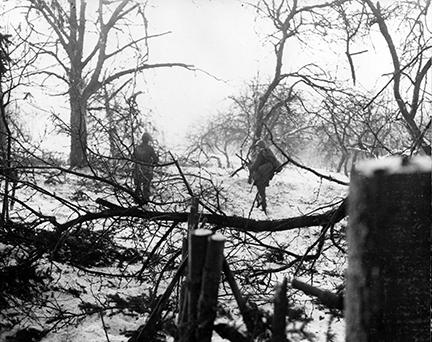 Ardennes-Battle of the Bulge. January 14, 1945 - Two parachute infantrymen advance through a snow-covered wooded section near Henumont, Belgium.