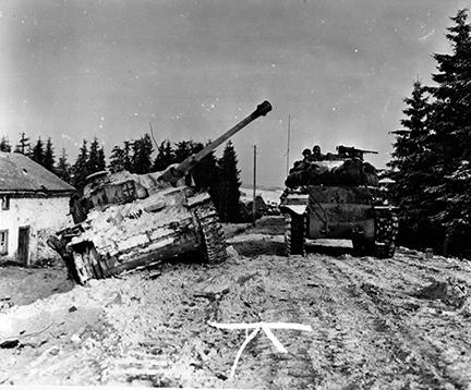 Ardennes-Battle of the Bulge. January 13, 1945 - Tank of 703rd Tank Battalion, 3rd Armored Division, moves past disabled German tank south of Langlir, Belgium.