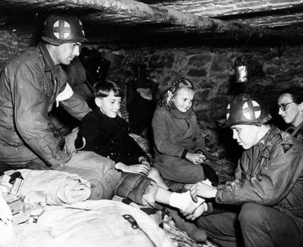 Ardennes-Battle of the Bulge. January 11, 1945 - Captain Charles S. Quinn (right) of Louisville, Kentucky, bandages gangrene infected foot of Belgian refugee child in cellar of house in Ottre, Belgium. Captain Quinn is a battalion surgeon with the 83rd Division, First Army.