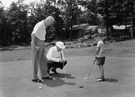 August 1, 1954 - Dwight D. Eisenhower, John Eisenhower, and David Eisenhower putt on green on the lawn of the main lodge while vacationing at Camp David