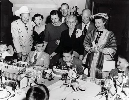 March 1956 - Roy Rogers, Mamie Eisenhower, Barbara Eisenhower, John Eisenhower, Elivera Doud, Dwight D. Eisenhower, and Dale Evans standing behind David Eisenhower at David's birthday party.