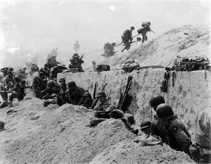 "June 9, 1944 - Taking a ""breather"" after gaining comparative safety offered by a concrete wall, American troops of the 8th Infantry Regiment, 4th Infantry Division, move over the crest of a hill to the interior of Northern France"