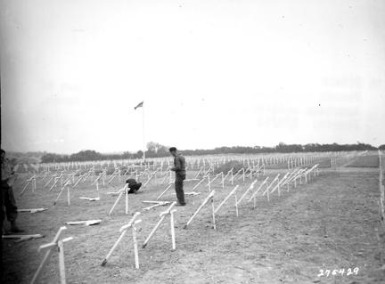 August 8, 1944 - French civilians place crosses at the graves of American soldiers in a cemetery on Omaha Beach, France