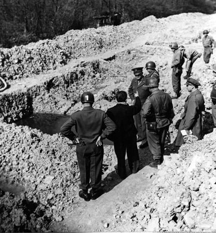 April 12, 1945 - Dwight D. Eisenhower, Omar Bradley, and George Patton are given a tour of Ohrdruf concentration camp. Here they visit a burial pit containing the charred remains of prisoners who were burned to death at Ohrdruf.