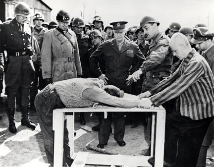 April 12, 1945 - Dwight D. Eisenhower watches as survivors of Ohrdruf demonstrate torture methods used at the camp