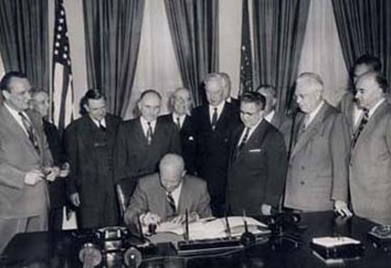May 6, 1954 - Dwight D. Eisenhower signs H.R. 8127. Standing behind Dwight D. Eisenhower from left to right: Sen. Styles Bridges, Rep. George A. Dondero, Rep. Clifford Davis, Sen. Francis Case, Rep. Homer Angell, Sen. Edward Martin, Rep. J. Harry McGregor, Sen. William Knowland, Sen. Prescott Bush, and an unidentified man.