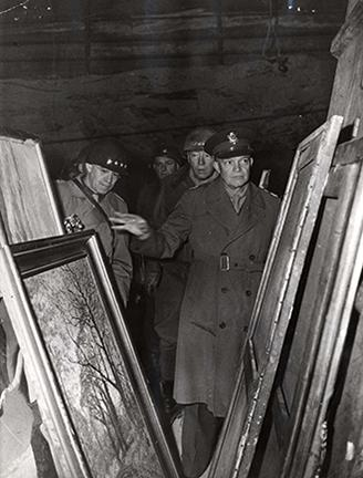 April 12, 1945 - General Dwight D. - Eisenhower inspects art treasures looted by the - Germans and stored in the depths of a salt mine in Germany along with gold, - silver, and paper currency. The mine was captured by U.S. Third Army troops. Behind - DDE are (left) General Omar Bradley and - (right) Lt. General George S. Patton