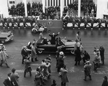 January 21, 1957 - Dwight D. Eisenhower waves to the crowd as he arrives at the inaugural parade reviewing stand