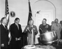 August 15, 1960 - Dwight D. Eisenhower holds the American flag which was carried in the capsule - retrieved from Discoverer XIII. [72-3525-5]