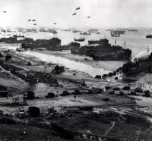 Panoramic view of supplies being brought ashore for Allied invaders