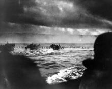 Coast Guard landing barges hitting the French coast with the first wave of the invasion. American soldiers wade ashore under heavy machine gun fire from Nazi beach nests.