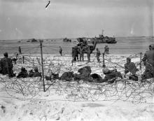 June 6, 1944 - German prisoners rest in a barb-wired enclosure on Utah Beach after being interrogated by American soldiers
